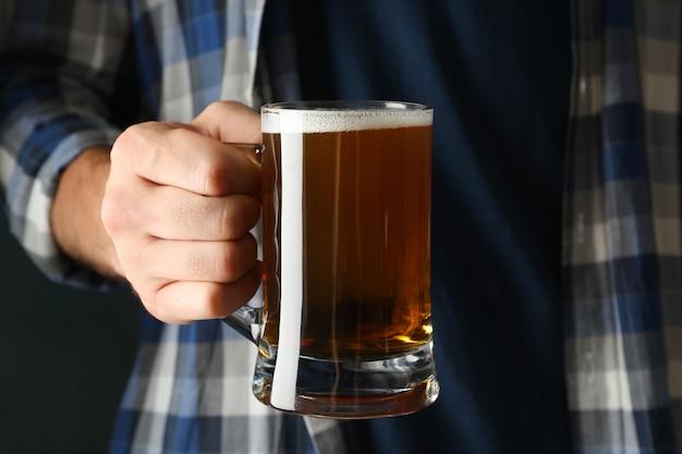 市松模様のシャツの男がビールのグラスを保持します。