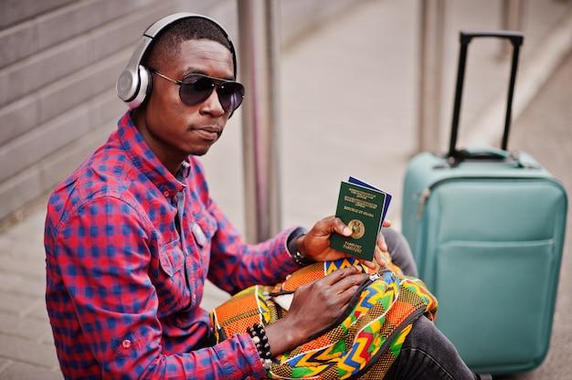 ガーナのパスポートを保持しているスーツケースとバックパックと市松模様のシャツ、サングラス、イヤホンの男