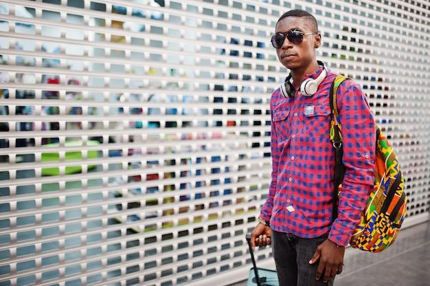 格子縞のシャツ、サングラス、ジーンズのスーツケースとバックパックの男