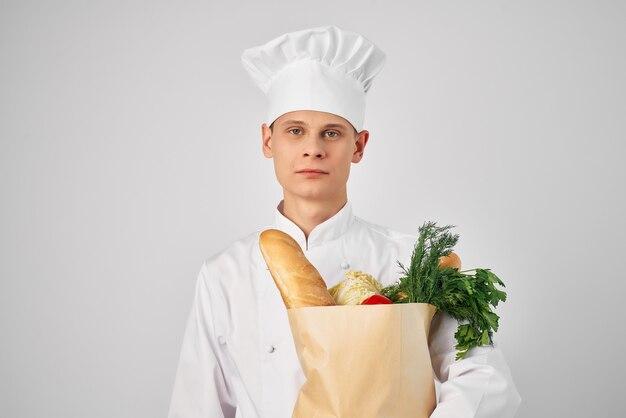 Человек в пакете одежды шеф-повара с продуктами готовит еду на кухне. фото высокого качества