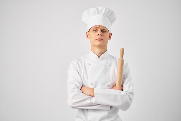 Человек в униформе кухни профессии шеф-повара работает светлый фон. фото высокого качества