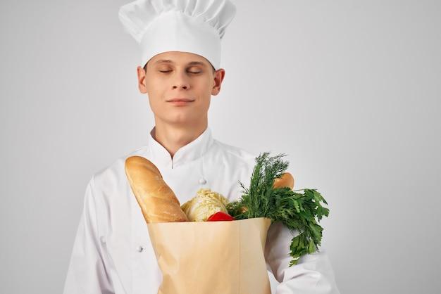 Человек в пакете одежды шеф-поваров с продуктами, готовящими еду на кухне