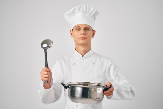手に鍋を持ったシェフの服を着た男が食べ物の明るい背景を準備します
