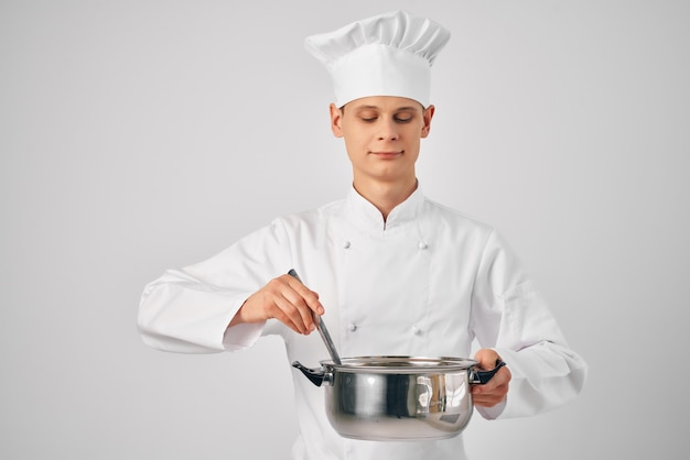 手に鍋を持ったシェフの服を着た男が食べ物の明るい背景を準備します。