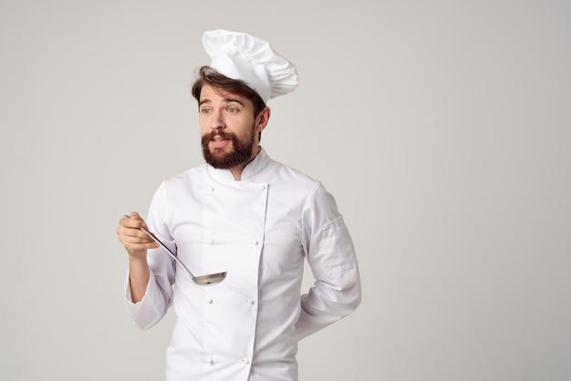 シェフの制服を着た男が料理のプロの料理を味わう