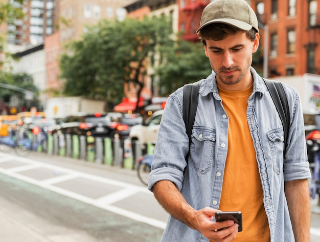 Человек в городе держит смартфон