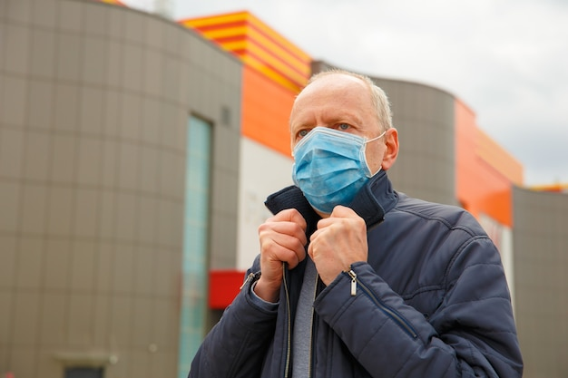 코로나 바이러스 확산을 보호하는 안면 마스크를 착용 한 도시 거리의 남자