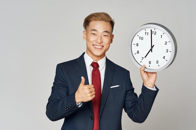 灰色の背景のトリミングされたビューで手に時計と古典的なスーツの男
