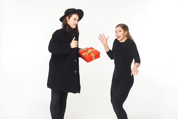 Мужчина в пальто и шляпе присутствует подарочная коробка смущает женщину. студия выстрел, изолированные на белом фоне