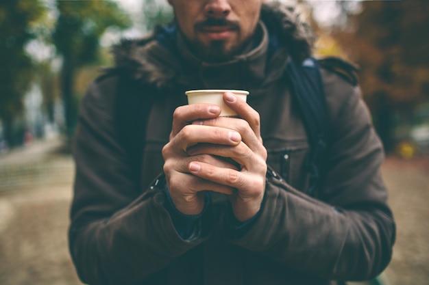 우유와 커피 라 떼 한 잔을 들고 코트에서 남자. 외로운 여자는 공원에서 눈 덮인가 황량한 거리에 서있다.