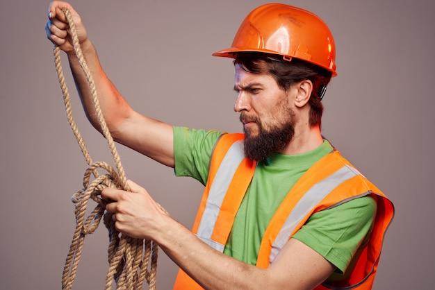 建設中の男性制服オレンジ色のヘルメットはベージュの背景の上にビューをトリミングしました。高品質の写真