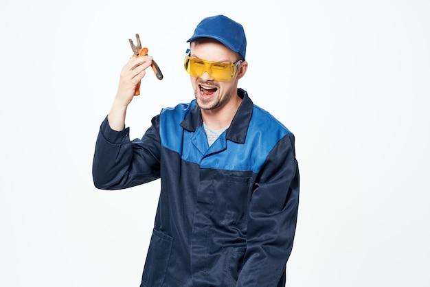 Человек в строительной форме с плоскогубцами в ремонте рук. фото высокого качества