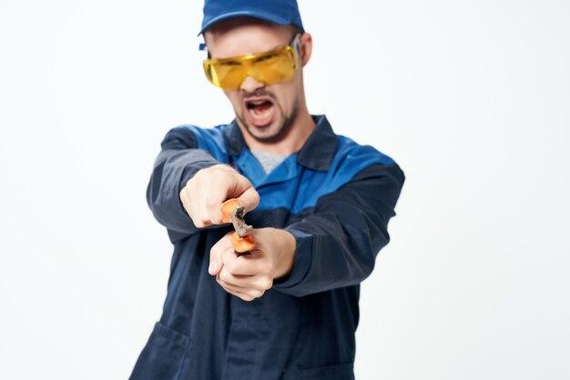 Человек в строительной форме с плоскогубцами в руках ремонтной службы