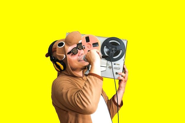 노래방에서 노래하는 소의 코스프레 의상을 입은 남자. 마이크를 들고 동물 잠옷 잠옷을 입은 남자. 릴 테이프 레코더로 재미있는 사진. 파티 아이디어. 디스코 레트로 음악.