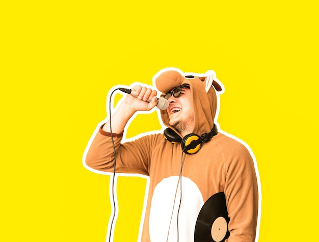 黄色の背景に分離されたカラオケを歌う牛のコスプレ衣装を着た男。マイクを保持している面白い動物のパジャマパジャマの男。面白い写真。パーティーのアイデア。ディスコ音楽。