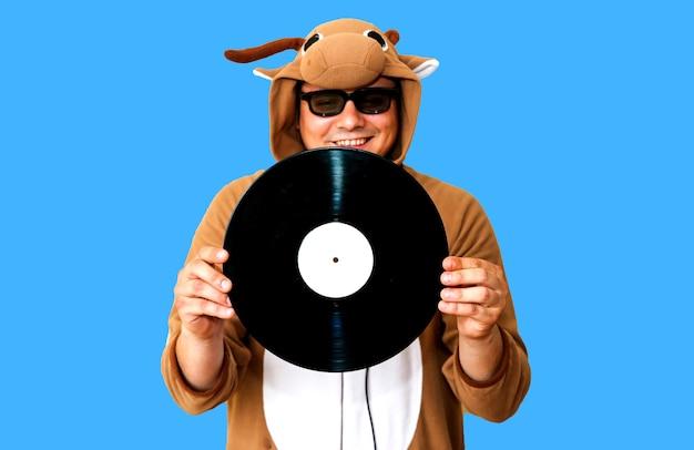 青い背景に分離された蓄音機レコードを持つ牛のコスプレ衣装の男。動物のパジャマの寝間着の男。パーティーのアイデアと面白い写真。ディスコレトロミュージック。
