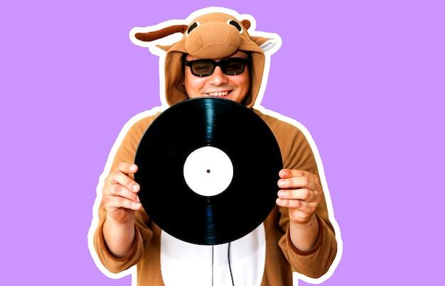 紫色の背景に分離された蓄音機レコードを持つ牛のコスプレ衣装の男。動物のパジャマの寝間着の男。パーティーのアイデアと面白い写真。ディスコレトロミュージック。