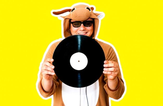 黄色の背景に分離された蓄音機レコードを持つ牛のコスプレ衣装の男。動物のパジャマの寝間着の男。パーティーのアイデアと面白い写真。ディスコレトロミュージック。