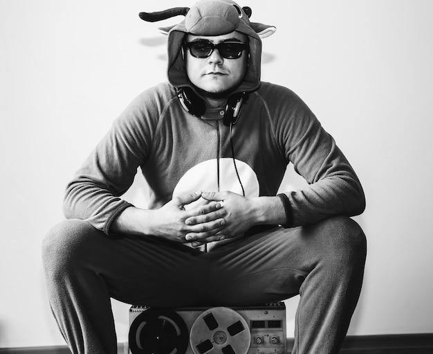 オープンリール式テープレコーダーで牛のコスプレ衣装を着た男。動物のパジャマの寝間着の男。パーティーのアイデアと面白い写真。ディスコレトロミュージック。黒と白。