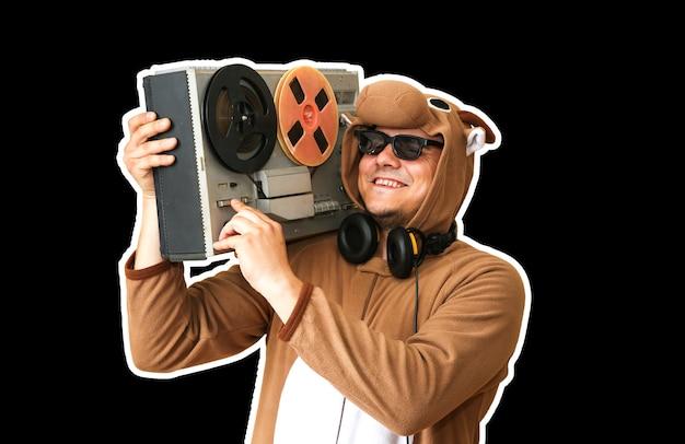 黒の背景に分離されたリールテープレコーダーと牛のコスプレ衣装の男。動物のパジャマの寝間着の男。パーティーのアイデアと面白い写真。ディスコレトロミュージック。