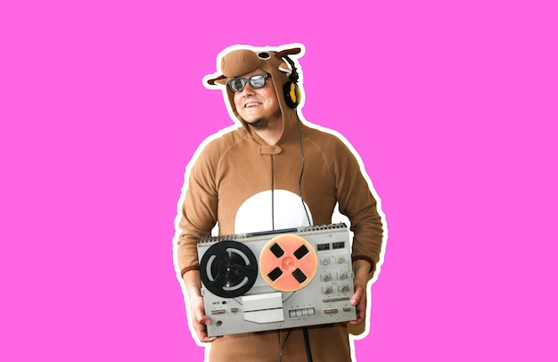 紫色の背景に分離されたリールテープレコーダーと牛のコスプレ衣装の男。動物のパジャマの寝間着の男。パーティーのアイデアと面白い写真。ディスコレトロミュージック。