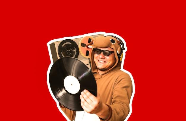 赤い背景に分離されたリールテープレコーダーと牛のコスプレ衣装の男。動物のパジャマの寝間着の男。パーティーのアイデアと面白い写真。ディスコレトロミュージック。