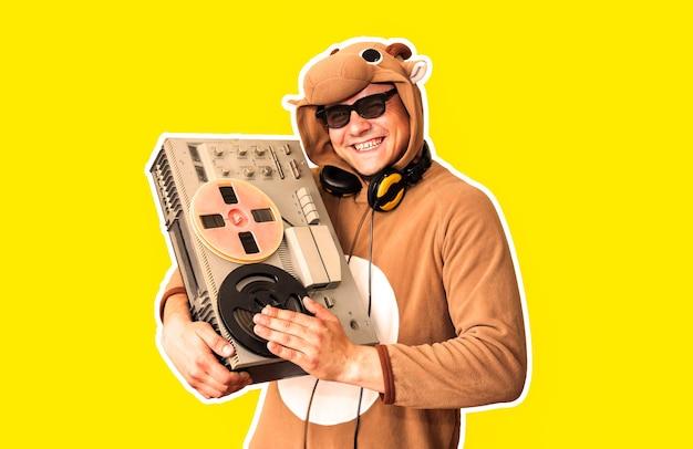 黄色の背景に分離されたリールテープレコーダーと牛のコスプレ衣装の男。動物のパジャマの寝間着の男。パーティーのアイデアと面白い写真。ディスコレトロミュージック。