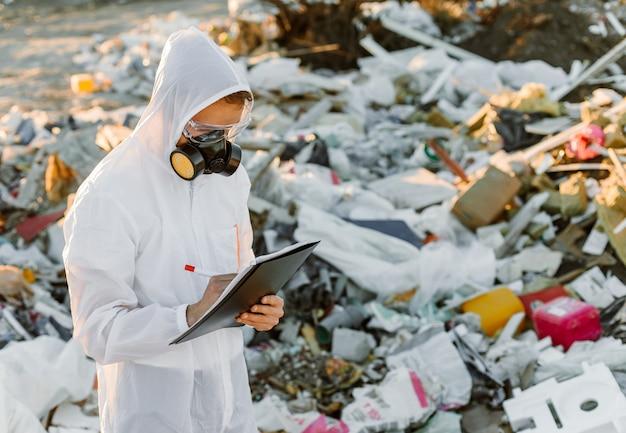 ゴミ箱のつなぎ服を着た男。調査する。生態学、環境汚染の概念。