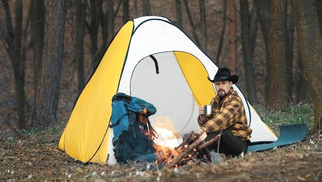 キャンプファイヤーと黄色と白のテントの隣に座ってお茶を飲むカウボーイハットとハイキング用品の男