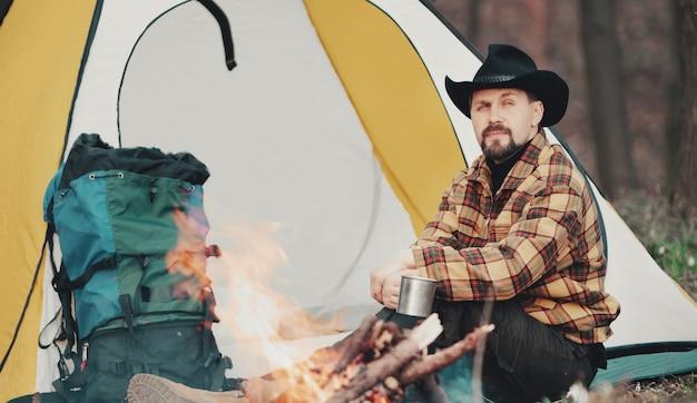 キャンプファイヤーと黄色と白のテントの隣に座ってお茶を持っているカウボーイハットとハイキングの服を着た男