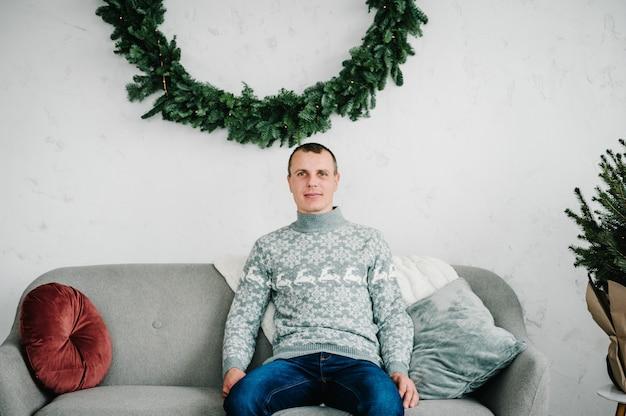Мужчина в уютной одежде возле елки с новым годом и рождеством