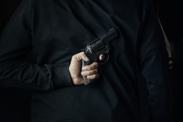 손에 총을 든 범죄자에 리볼버가 달린 어두운 옷을 입은 남자가 공격을 위해 총기를 들고 있습니다...