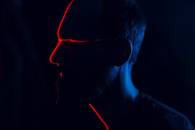 Человек в темноте с лицом, освещенным красным лазером сканирования по контуру.