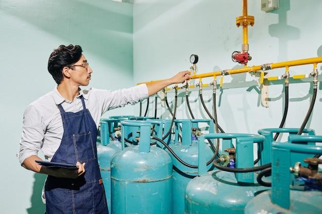 Человек в джинсовом фартуке держит планшетный компьютер и контролирует давление в газовых трубах
