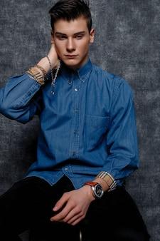 Человек в джинсовой рубашке, руки на бедрах, серый фон. концепция образа жизни людей. копируйте пространство для копирования. выпрямление рукавов при взгляде в сторону. цепь под рукой