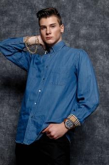 Человек в джинсовой рубашке, руки на бедрах, серый фон. концепция образа жизни людей. копируйте пространство для копирования. выпрямление рукавов взглядом в сторону