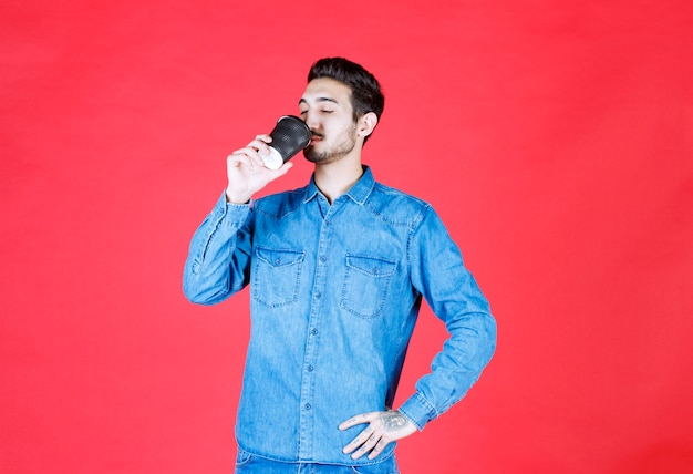 Мужчина в джинсовой рубашке держит черную одноразовую чашку с напитком и пьет ее.