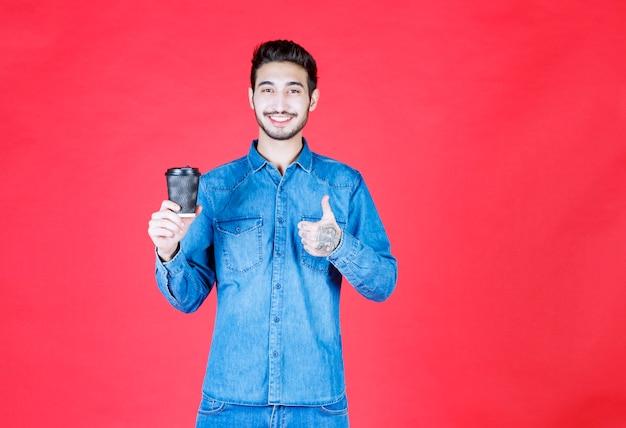 Человек в джинсовой рубашке держит черную одноразовую чашку напитка и наслаждается ею.