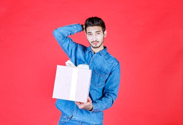 Мужчина в джинсовой рубашке держит фиолетовую подарочную коробку, перевязанную белой лентой, и выглядит смущенным и задумчивым.