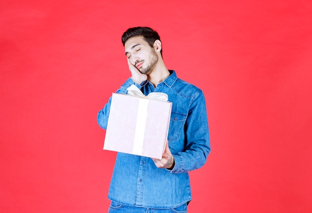 Мужчина в джинсовой рубашке держит фиолетовую подарочную коробку, перевязанную белой лентой, и выглядит сонным и усталым.