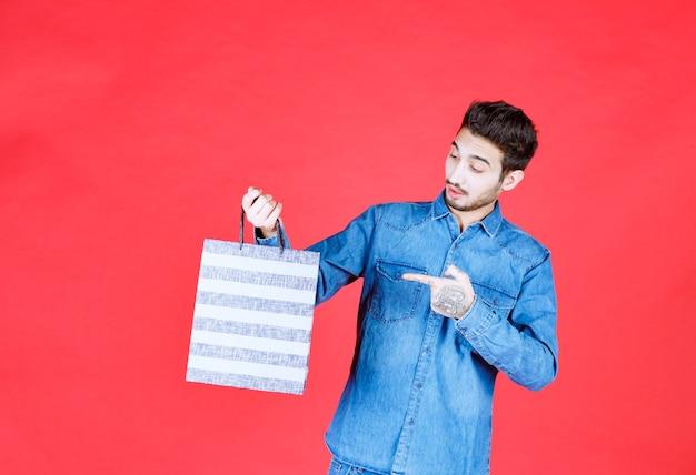 Мужчина в джинсовой рубашке, держащий полосатую коробку для покупок, выглядит удивленным и задумчивым.