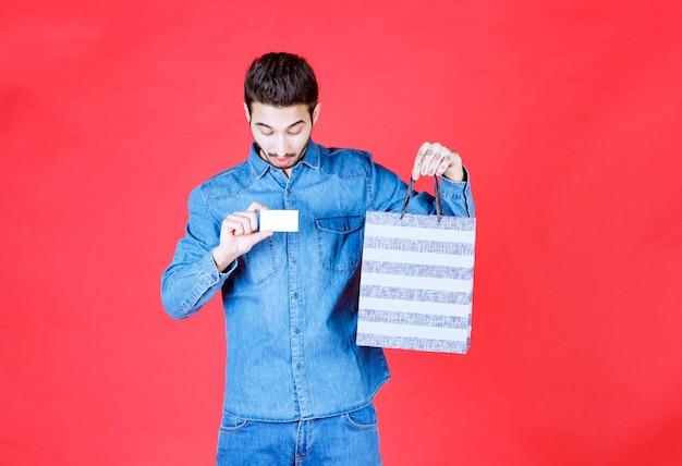 Мужчина в джинсовой рубашке держит полосатую коробку для покупок и представляет свою визитную карточку.