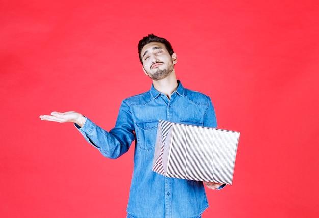 Человек в джинсовой рубашке держит серебряную подарочную коробку и указывает куда-то.