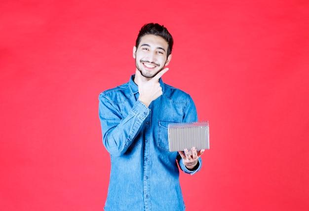Человек в джинсовой рубашке держит серебряную подарочную коробку.