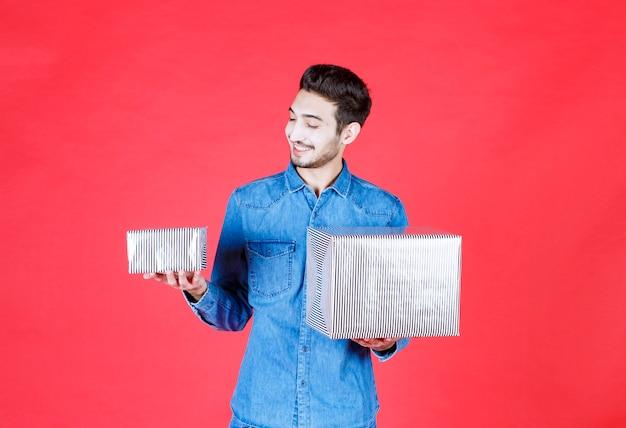 Мужчина в джинсовой рубашке, держа в обеих руках две серебряные подарочные коробки.
