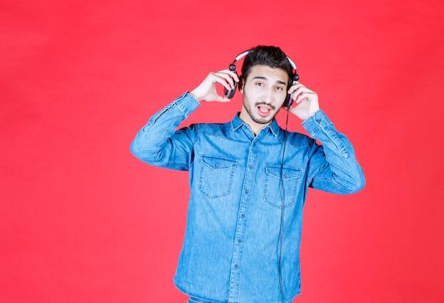 Человек в джинсовой рубашке в наушниках и слушает новые треки.