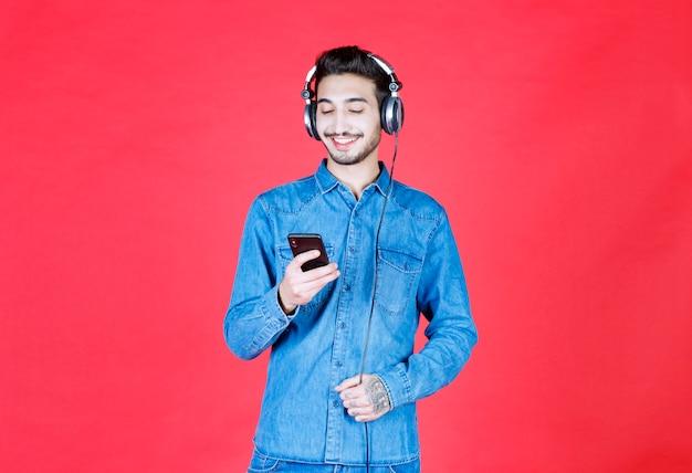 헤드폰을 끼고 셀카를 찍거나 화상 통화를하는 데님 셔츠를 입은 남자.