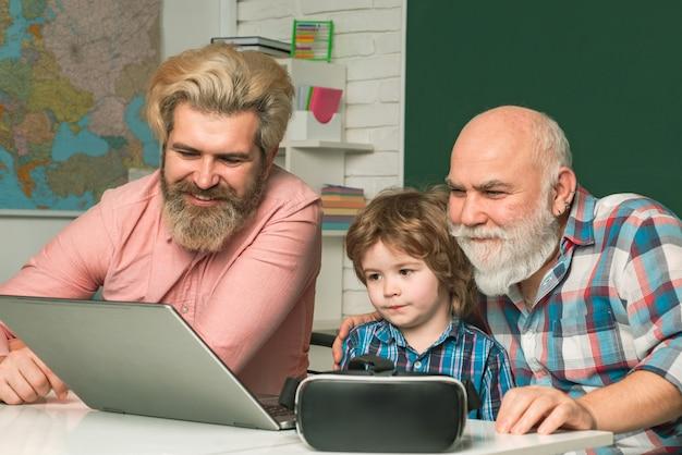 ノートパソコンの画面のソーシャルネットワークの古い祖父の父と息子がnoteboを使用して見ている別の男...