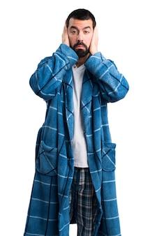 Человек в халате, покрывающий уши
