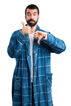 Man in dressing gown making good-bad sign
